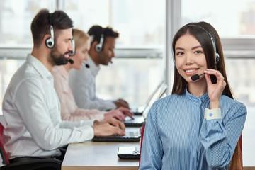 Korean girl wearing headset. Portrait of smiling girl adjusting headset in bright office.