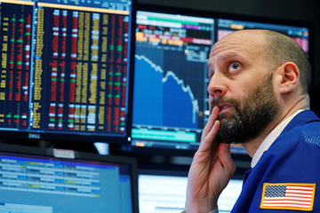 A trader reacts as he watches screens on the floor of the New York Stock Exchange in New York