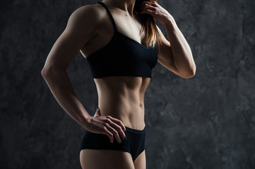 Side view of muscular fitness female model standing on black background. Young woman wearing sports bra looking down in thought.