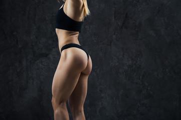 Close-up of a perfect female body over dark studio background
