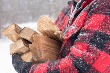 Closeup of man carrying bundle of firewood through the snow