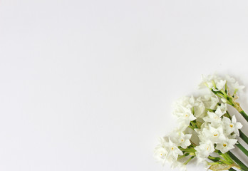 Spring styled stock photo. Easter concept. Feminine desktop scene with bouquet of narcissus, daffodil flowers on white table background. Empty space. Flat lay, top view.