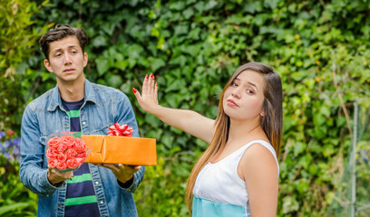 Close up of blurred man holding a gift and flowers with shocked face after see his girlfriend stretching her arm ignoring him , friendzone concept