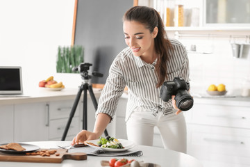 Young woman taking still life pictures in kitchen