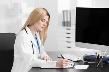 Female doctor filling up application form in consultation room