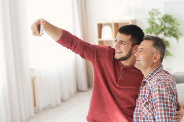 Young man taking selfie with his dad at home