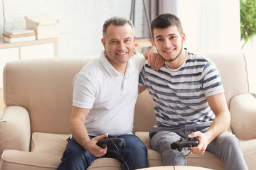 Mature man playing video game with his son at home