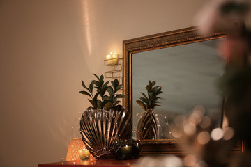 Vase with plant and beautiful mirror on table
