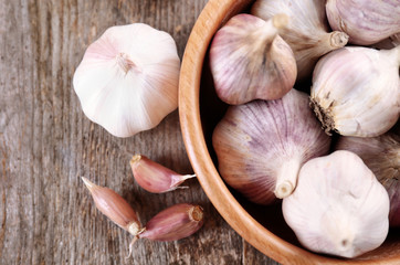 Bowl with fresh garlic on wooden table