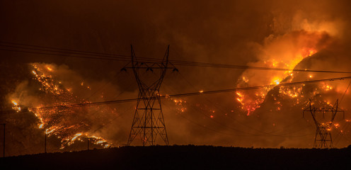 Large wildfire in California on hillside behind silhouette of powerlines