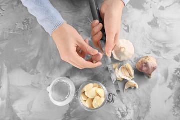 Woman peeling garlic at table