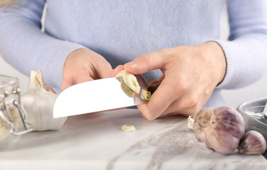 Woman cutting garlic at table