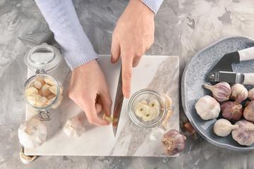 Woman cutting garlic on board at table