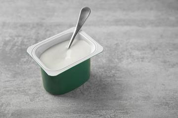 Plastic cup with yogurt on grey background