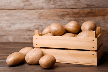 Wooden container with fresh raw potatoes on table