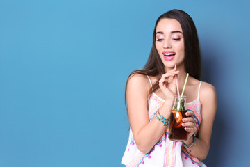 Young woman with tasty refreshing lemonade on color background