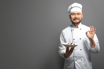 Handsome male chef holding plate with dish on gray background