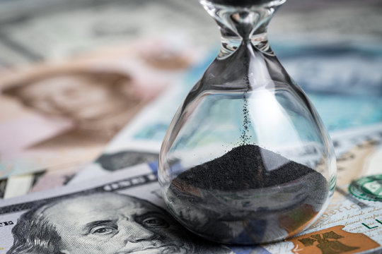 Time counting down for world financial crisis concept, sandglass or hourglass on US dollar money and world international banknotes, can use as long term investment or savings for future