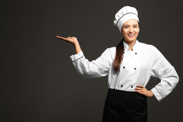 Beautiful female chef on dark background