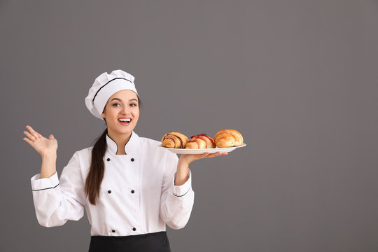 Beautiful female chef holding plate with croissants on gray background