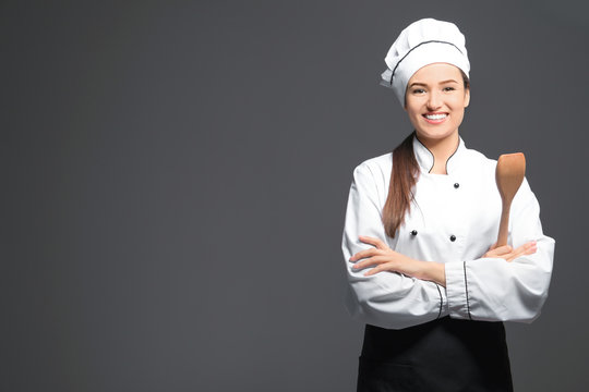 Beautiful female chef with wooden spoon on dark background