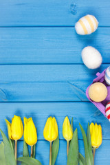 Bouquet of fresh yellow tulips and Easter eggs wrapped woolen string
