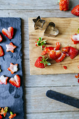 Close-up of whole and cut strawberries, with star and heart molds