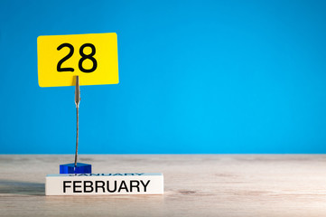 February 28th. Day 28 of february month, calendar on little tag at blue background. Winter time. Empty space for text, mockup