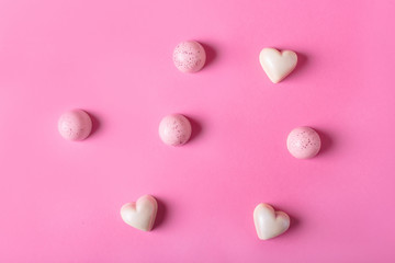 White candy in the shape of heart on a pink background. Pink Chocolate.