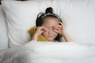 テディーベアーと一緒に眠る女の子