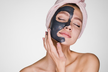 the amazed woman with a towel on her head apply a cleansing mask on her face