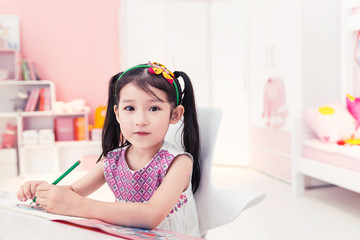 Portrait of cute girl drawing with colored pencil at home