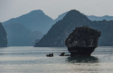 man fishing in small boat among limestone karsts in Ha Long Bay, Vietnam