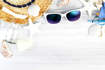 Wall Mural - Summer Beach accessories (White sunglasses,starfish,straw hat,glass bottle,shell) on white plaster wood table top view,Summer vacation concept,Leave space for adding text..