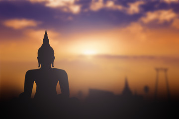 Silhouette Buddha with blurred tourist attraction in thailand on golden sunset background.