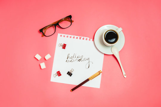 """Flatlay with glasses, pen, clips, cup of coffee and  white page with handlettering """"Hello Monday"""". Business concept. Pink background."""