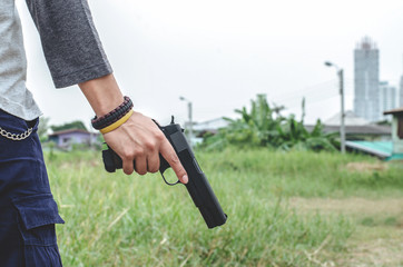 Killer holding a gun side him , cropped shot of man holding gun in hand.