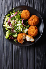 Homemade codfish cake and fresh salad closeup on a plate. Vertical top view