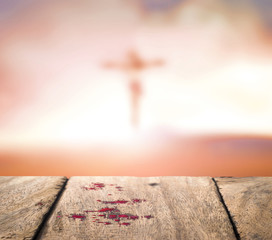 Good Friday concept: Blood on wood and blurred Jesus Christ on the cross sunset background