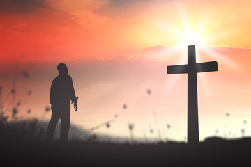 Good Friday concept: Silhouette human standing over blurred crown of thorns and the cross on nature background.