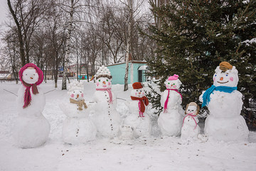 family of snowmen at the children's winter festival, in a hat and scarf