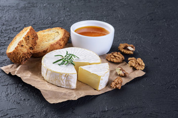 Camembert cheese, toasts, rosemary, honey and walnuts on a dark background.