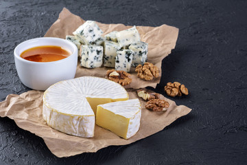 Camembert cheese, blue cheese, honey and walnuts on a dark background.