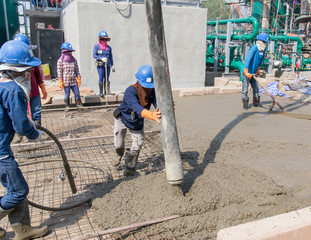 Workers at the construction site placing concrete road slab