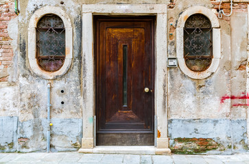 Old building with a wooden door and ornate windows in Venice Italy