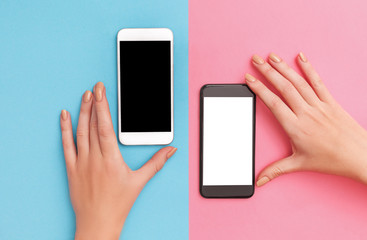 female hands hold two phones black and white.