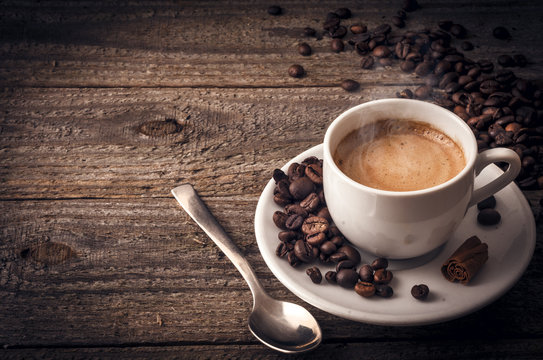 Cup of coffee on wooden table with cinnamon
