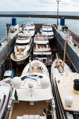 Yachts loaded up onto a transport ship ready to be shipped across the atlantic to Florida.