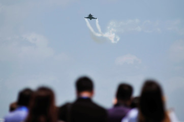 Spectators look at a Royal Thai Air Force (RTAF) JAS-39 C/D Gripen fighter aircraft during an aerobatic display at the Singapore Airshow