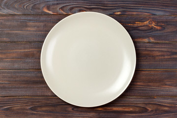 empty matte round plate on wood table. top view